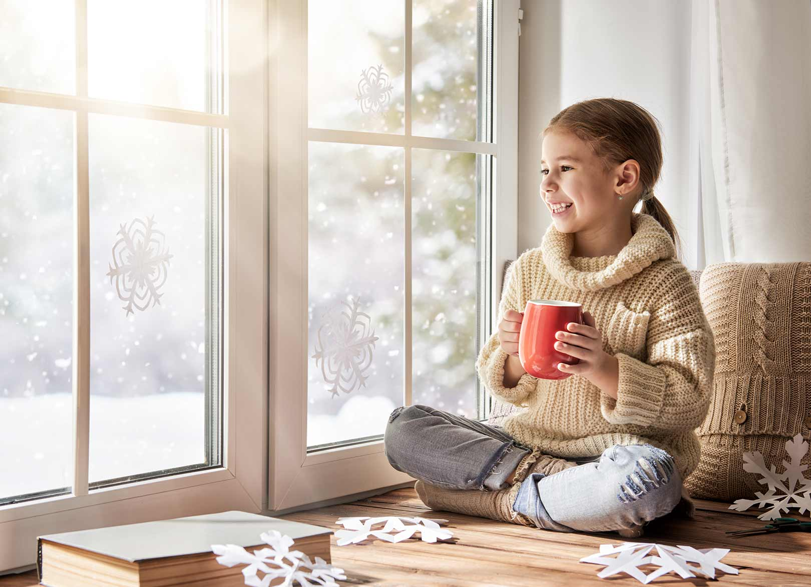 Young girl in beige jumper sat inside, holding mug of hot chocolate watching snowflakes