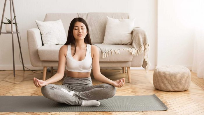 Asian Girl Practicing Yoga In Lotus Position, Meditating in Morning at Home