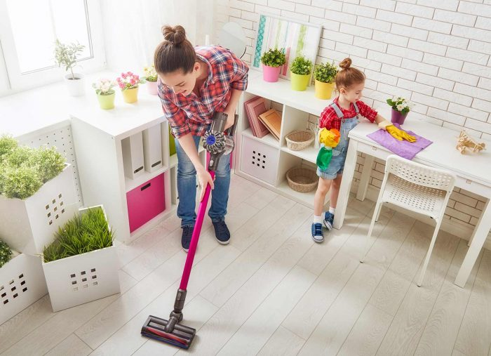 Mum and daughter cleaning children's playroom