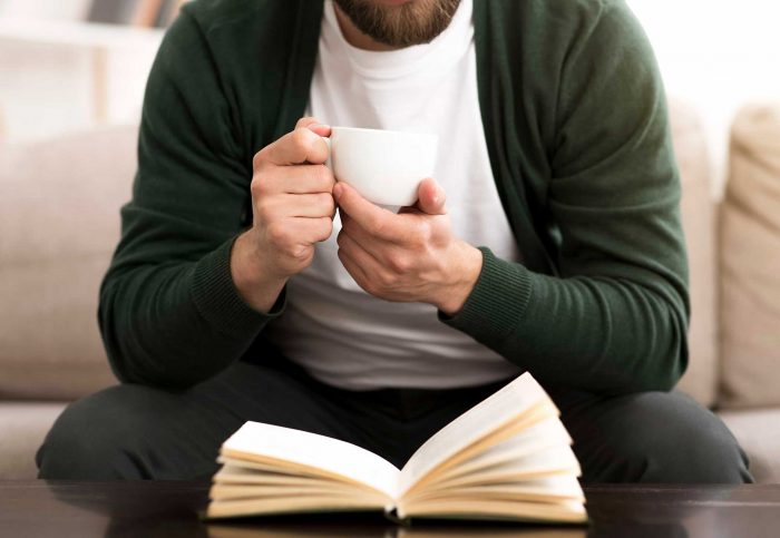 Man drinking coffee, sitting on a sofa at home and reading a book to relax