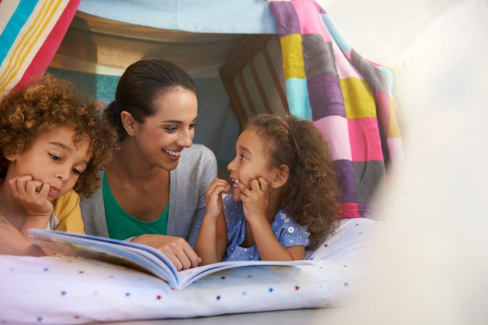 Mum and daughters in a homemade fort reading books