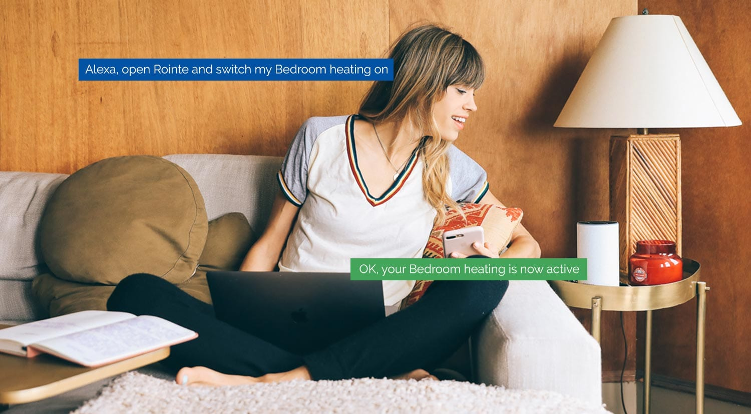 Woman on sofa instructing Amazon Alexa to switch on her Rointe bedroom heating