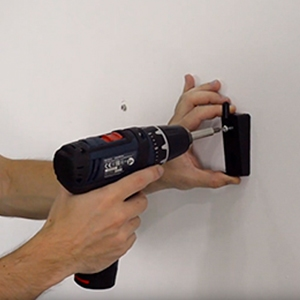 Step 3: fixing the upper bracket to the wall for a Rointe radiator using electric drill and screws