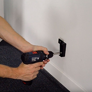 Step 4: fixing the lower bracket of a Rointe radiator to the wall using electric drill and screws