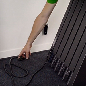 Step 6: uncoiling the cable and plug from the back of a Rointe radiator
