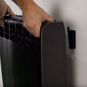 Step 7: lifting a Rointe radiator into the wall brackets