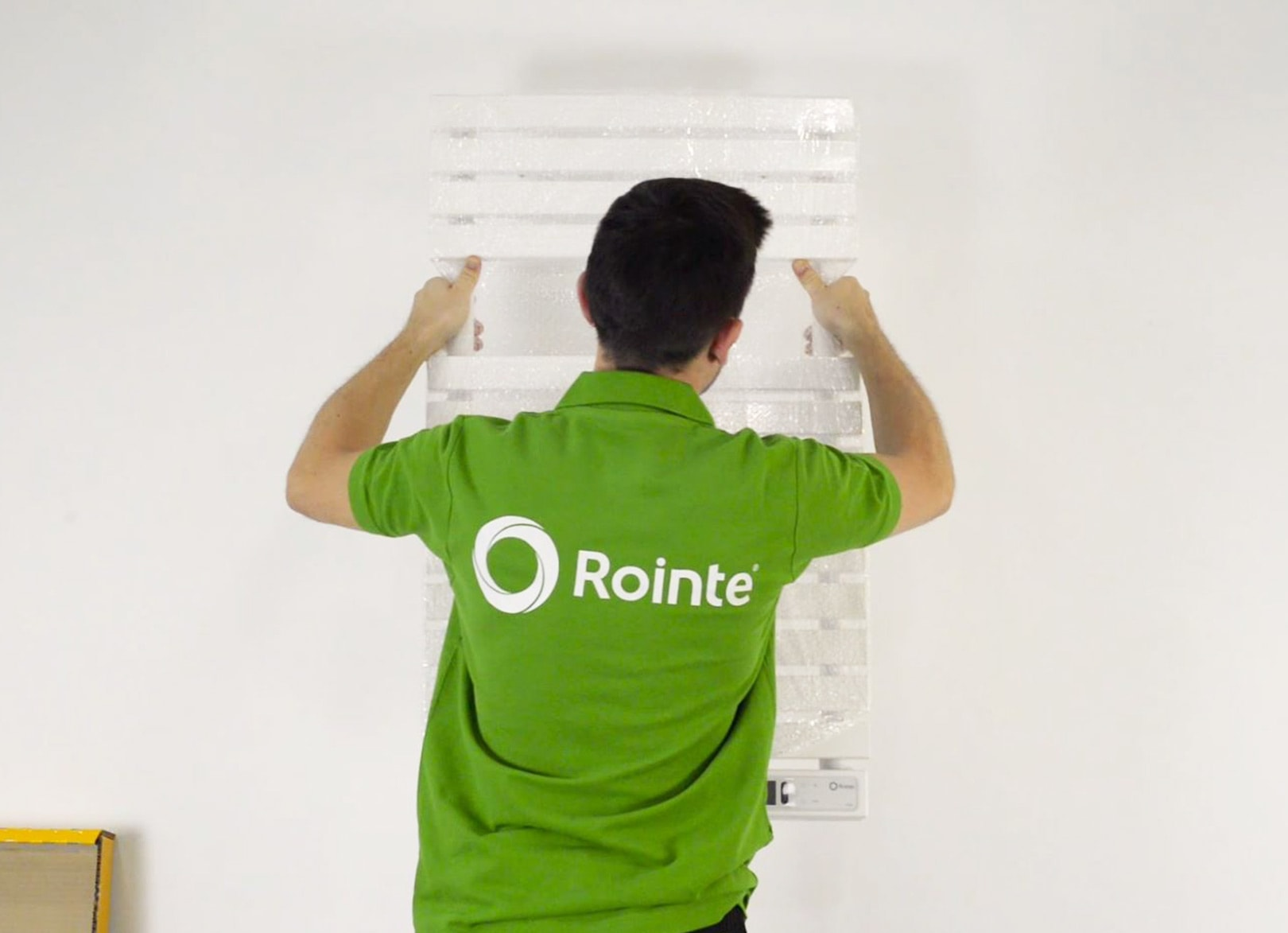 Rointe installer mounting a Rointe towel rail to the wall