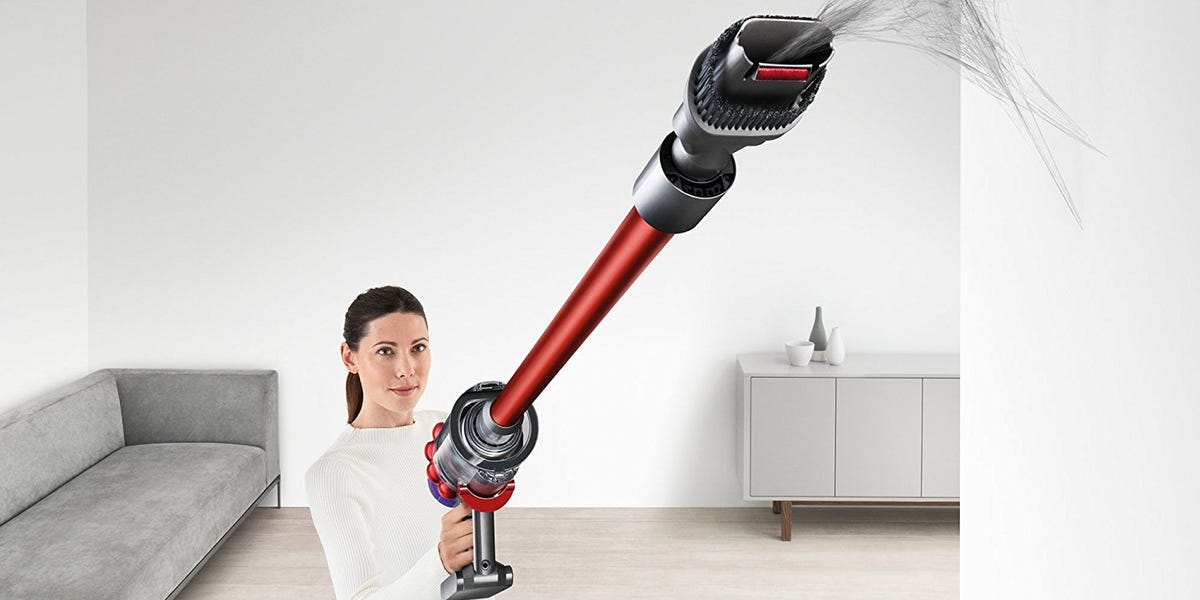 Woman using vacuum to remove dust from ceilings and radiators